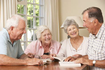 old man smiling: Group Of Senior Couples Attending Book Reading Group