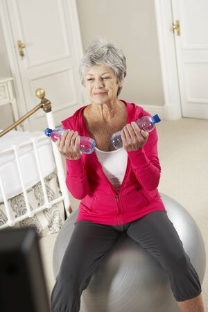 keeping room: Senior Woman Exercising Whilst Watching Fitness DVD On Television