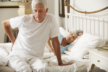 cama: Hombre mayor que sufre de dolor de espalda levantarse de la cama Foto de archivo