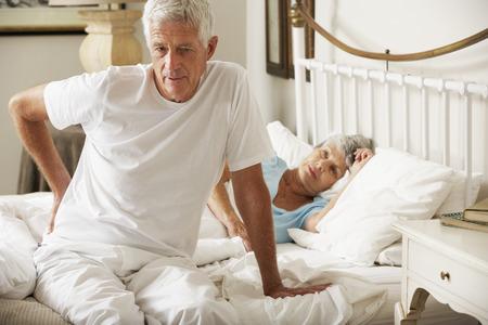 Senior man lijdt aan rugpijn uit bed Stockfoto