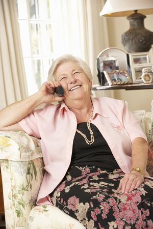 persona sentada: Jubilado mayor de la mujer que se sienta en el sofá en país en el teléfono
