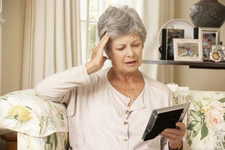 Ongelukkige Gepensioneerde senior vrouw zitten op de bank thuis op zoek Foto Stockfoto