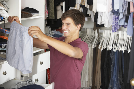 choosing clothes: Teenage Boy Choosing Clothes From Wardrobe In Bedroom