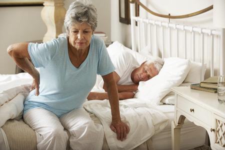 Hogere vrouw die lijdt aan rugpijn uit bed Stockfoto