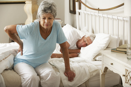 male senior adult: Senior Woman Suffering From Backache Getting Out Of Bed