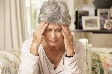 dementia: Unhappy Retired Senior Woman Sitting On Sofa At Home Stock Photo