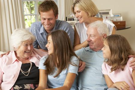 Multi Generation Family Group Sitting On Sofa Indoors