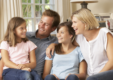 Family Group Sitting On Sofa Indoors Stock Photo