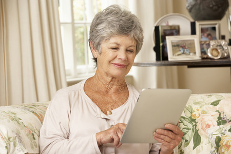 silver surfer: Retired Senior Woman Sitting On Sofa At Home Using Tablet Computer Stock Photo