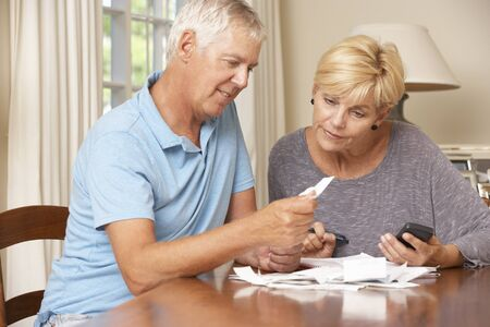 bill: Mature Couple Checking Finances And Going Through Bills Together