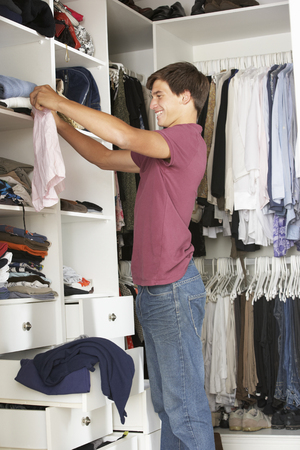 boxer shorts: Teenage Boy Choosing Clothes From Wardrobe In Bedroom
