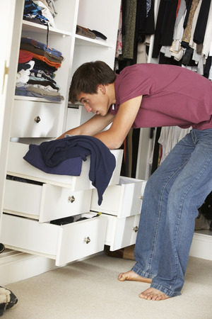 messy clothes: Teenage Boy Choosing Clothes From Wardrobe In Bedroom