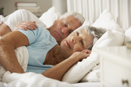 insomniac: Senior Woman Having Difficulty In Sleeping In Bed With Husband Stock Photo