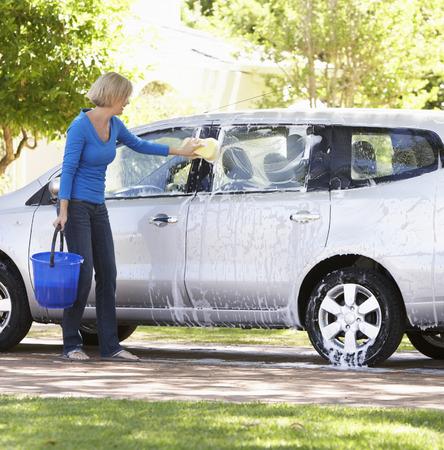 washing car: Woman Washing Car In Drive Stock Photo