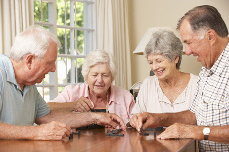 dominoes: Group Of Senior Couples Enjoying Game Of Dominoes At Home