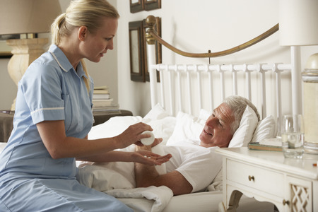 palliative: Nurse Giving Senior Male Medication In Bed At Home