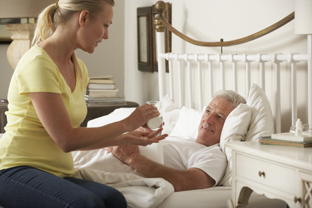 palliative: Adult Daughter Giving Senior Male Parent Medication In Bed At Home