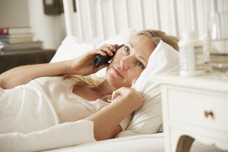 personne malade: Femme malade dans son lit � la maison en parlant au t�l�phone