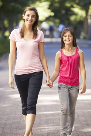 10 year old: Mother And Daughter Walking Through Summer Park