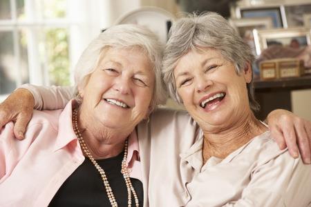 Retrato De Dos Jubilados Mayores Amigos femeninos sentado en el sofá Foto de archivo