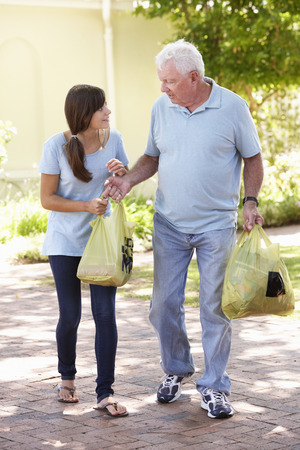 Teenage Granddaughter Helping Grandfather With Shopping Stock Photo