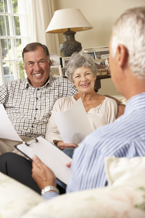 financial advisor: Retired Senior Couple Sitting On Sofa Talking To Financial Advisor
