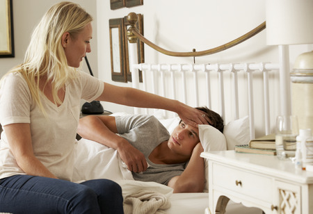 Sick Teenage Boy In Bed At Home Being Cared For By Mother Stock Photo