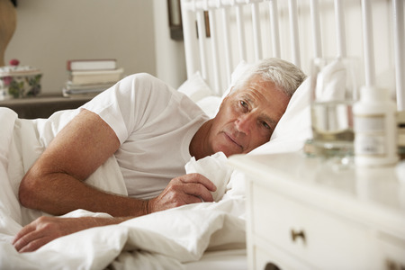 personen: Zieke Hogere Mens in bed thuis Stockfoto