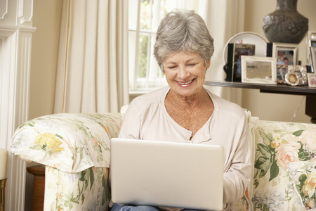silver surfer: Retired Senior Woman Sitting On Sofa At Home Using Laptop Stock Photo