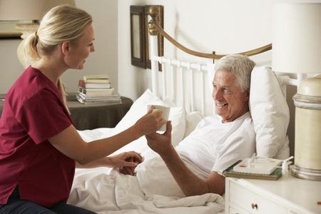 ヘルスケア: 自宅のベッドでシニア男性温かい飲み物を与えて健康の訪問者