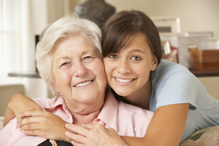grown ups: Teenage Granddaughter Visiting Grandmother At Home Stock Photo