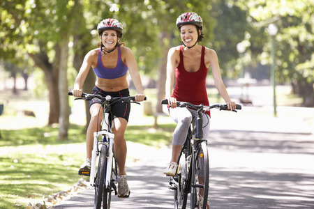 Two Women Cycling Through Park Stock Photo