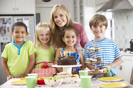 children birthday: Group Of Children Standing With Mother By Table Laid With Birthday Party Food