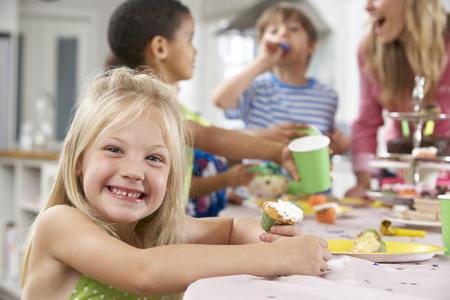five years old: Group Of Children Enjoying Birthday Party Food At Table Stock Photo