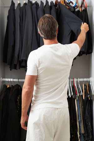 choosing clothes: Man Standing In Front Of Wardrobe Choosing Clothes Stock Photo