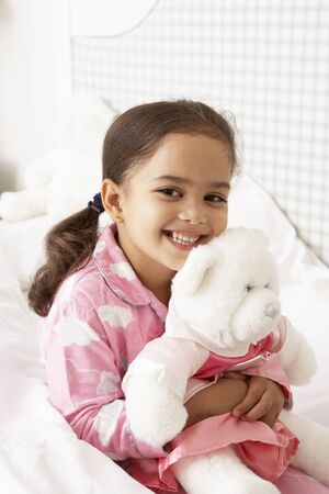 cuddly toy: Young Girl Wearing Pajamas In Bed With Cuddly Toy