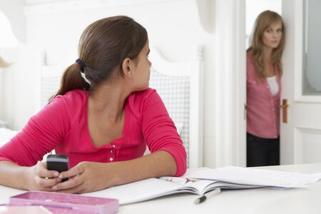 meant: Mother Catches Daughter Using Phone When Meant To Be Studying Stock Photo