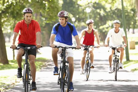 grupo de hombres: Grupo de hombres en paseo del ciclo a través de parque Foto de archivo