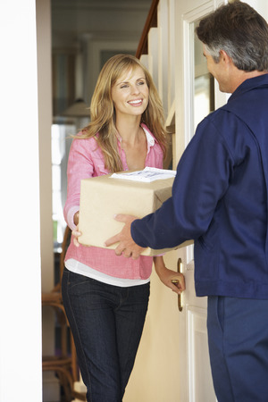 courier: Woman Signing For Package Delivered By Courier Stock Photo