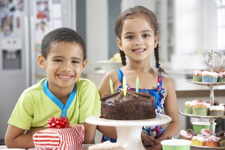 5 year old girl: Two Children Standing By Table Laid With Birthday Party Food