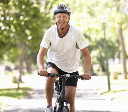 ciclismo: Hombre maduro Ciclismo a trav�s de parque Foto de archivo