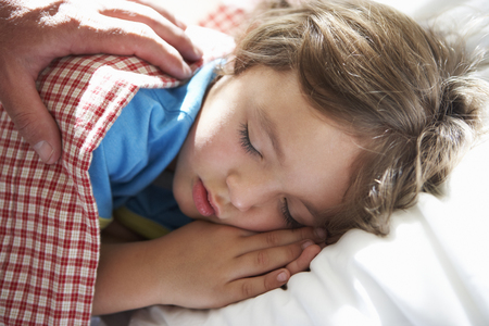 Parent Waking Young Boy Asleep In Bed Stock Photo