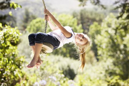 Young Girl Having Fun On Rope Swing