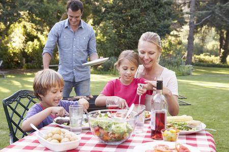 hombre comiendo: Familia que disfruta de la barbacoa en jardín junto
