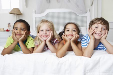 Cuatro Niños Jugando En La Cama Juntos Foto de archivo - 42247583