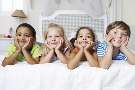indoors: Four Children Playing On Bed Together Stock Photo