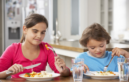 5 10 year old girl: Two Children Having Meal In Kitchen Together Stock Photo