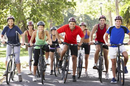 andando en bicicleta: Grupo de ciclistas en paseo del ciclo a través de parque Foto de archivo