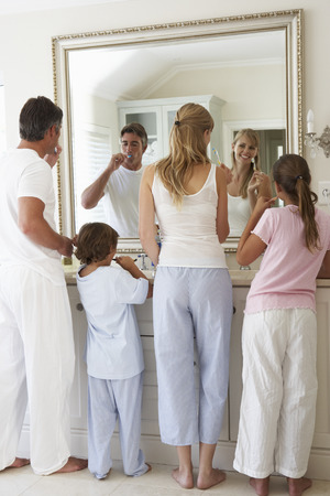 Family Brushing Teeth In Bathroom Mirror