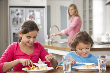 10 year old: Two Children With Mother Having Meal In Kitchen Together
